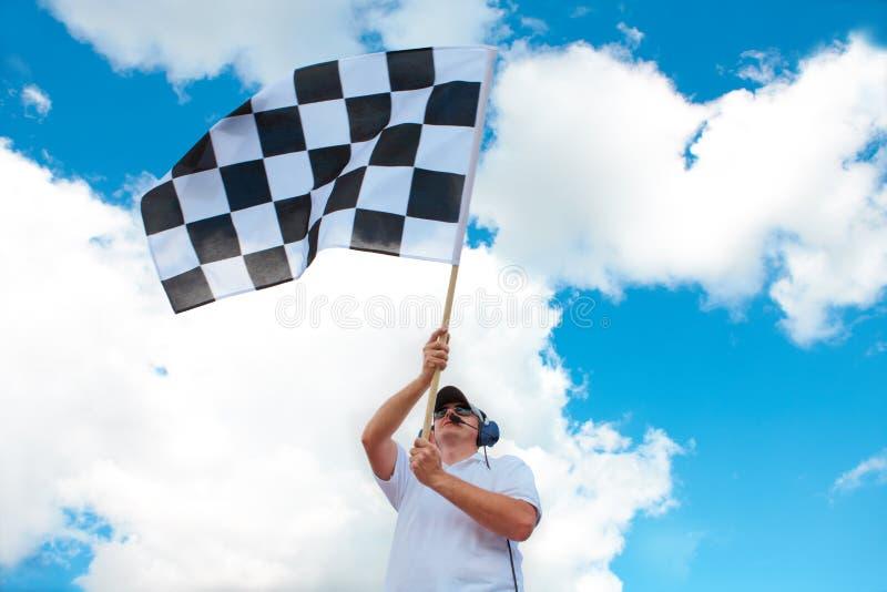Mens die een geruite vlag op een toevoerkanaal golft stock afbeelding