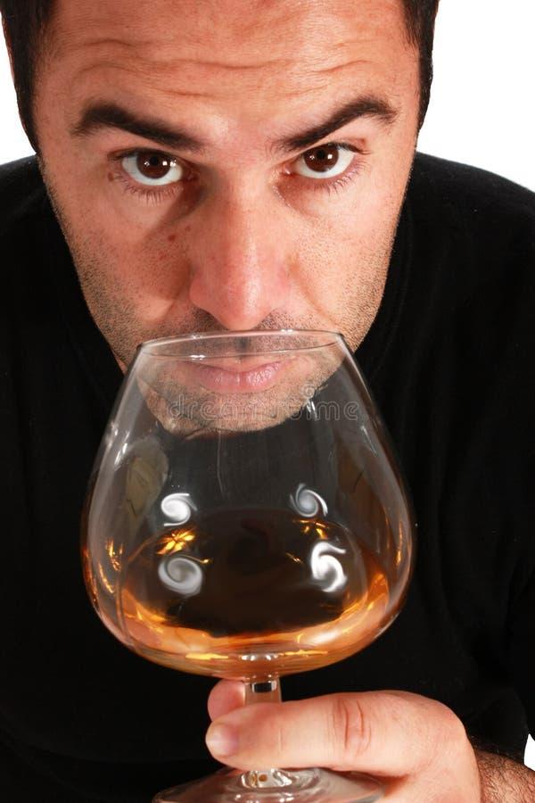 Mens die een glas whisky ruikt royalty-vrije stock afbeelding