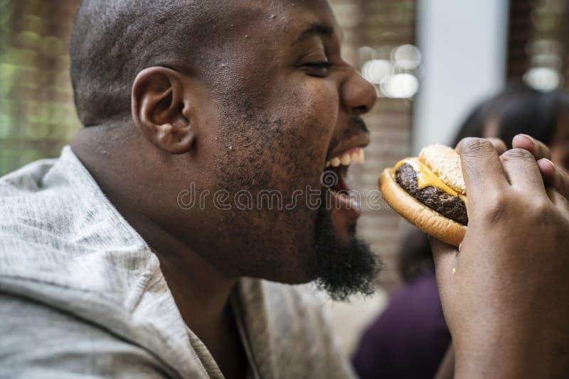 Mens die een grote hamburger eten royalty-vrije stock fotografie
