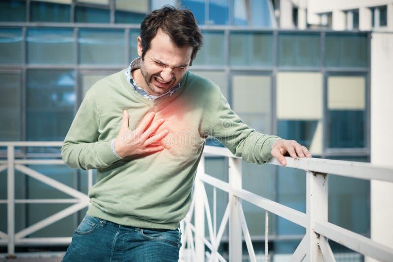 Mens die een grote pijn op de borst en het instorten voelen stock afbeelding