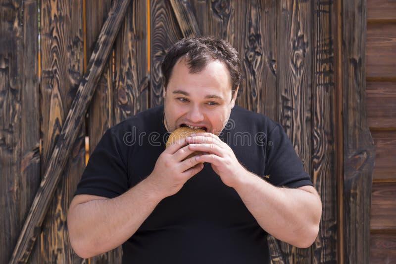 Mens die een Hamburger eet royalty-vrije stock foto's