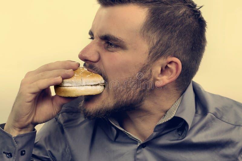 Mens die een Hamburger eet royalty-vrije stock fotografie