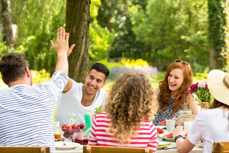 Mens die een hoogte vijf aan vrienden en meisjes geven die tijdens lu lachen royalty-vrije stock afbeelding