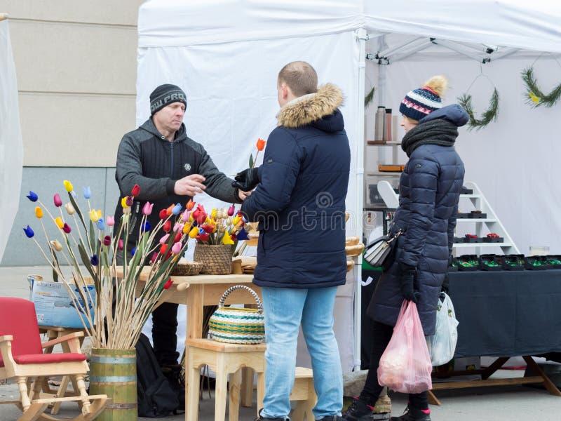 Mens die een houten rode tulp kopen royalty-vrije stock fotografie