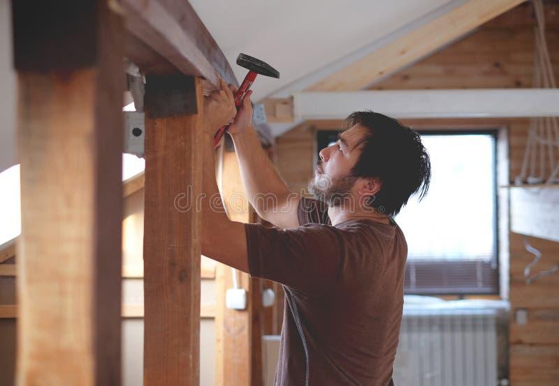 Mens die een huis en workimg met hamer en hout bouwen royalty-vrije stock foto's