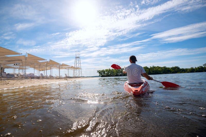 Mens die een kajak in het overzees naast het strand paddelen royalty-vrije stock fotografie