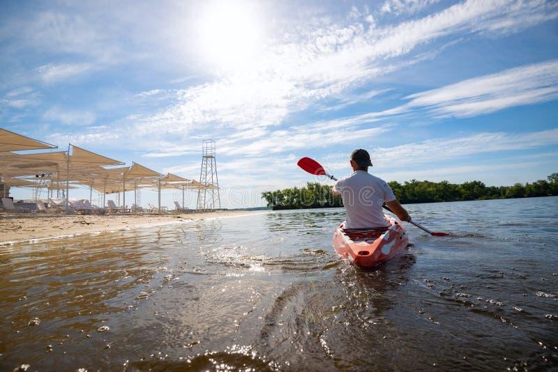 Mens die een kajak in het overzees naast het strand paddelen royalty-vrije stock foto