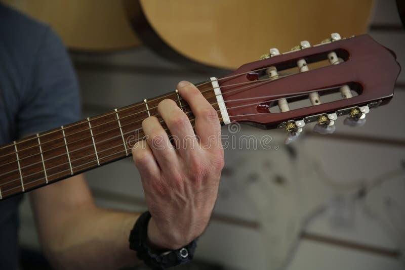 Mens die een klassieke gitaar spelen Plukt omhoog de koorden op de gitaar met de hand stock foto