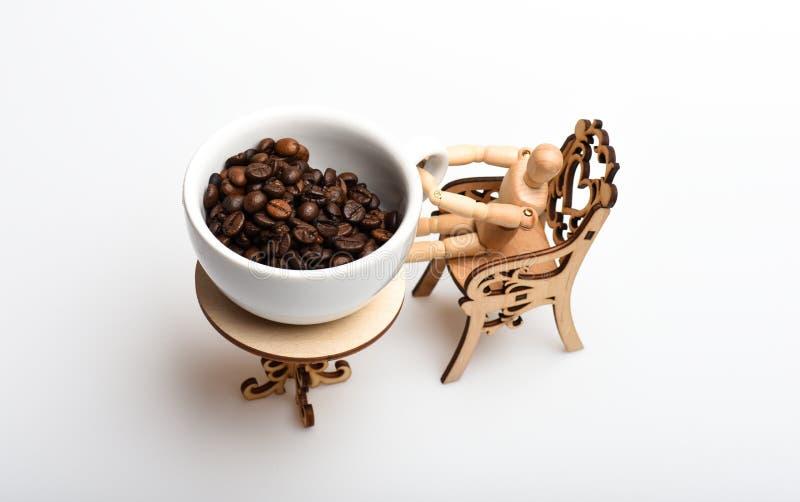 Mens die een koffiepauze neemt Bonen van de mok kijkt de verse geroosterde koffie reuze op uiterst kleine lijst Kop koffiebonen d royalty-vrije stock foto's