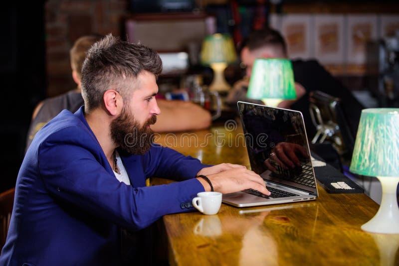 Mens die een koffiepauze neemt Zit de mensen gebaarde zakenman barteller met laptop en kop van koffie Creeer de blog van het inho royalty-vrije stock afbeeldingen
