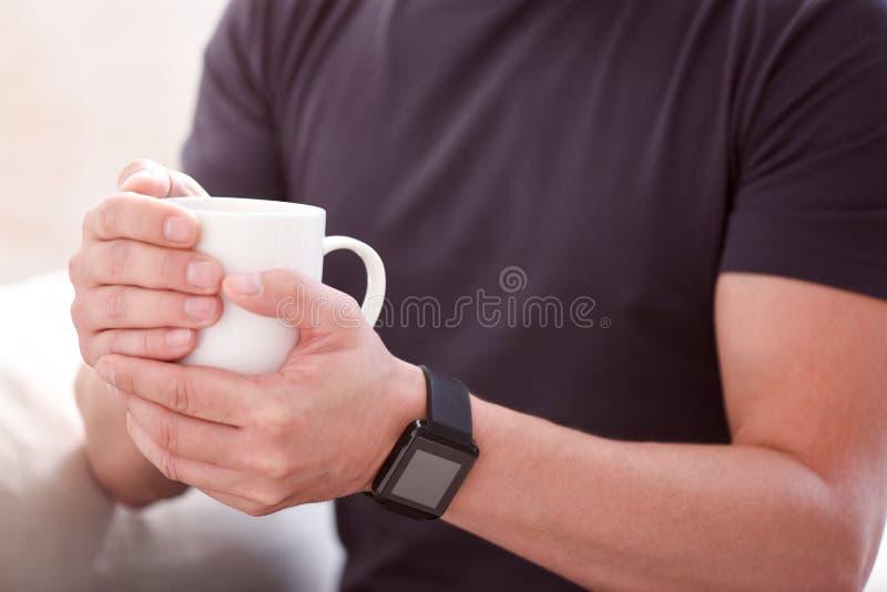 Mens die een kop in beide handen houden stock fotografie