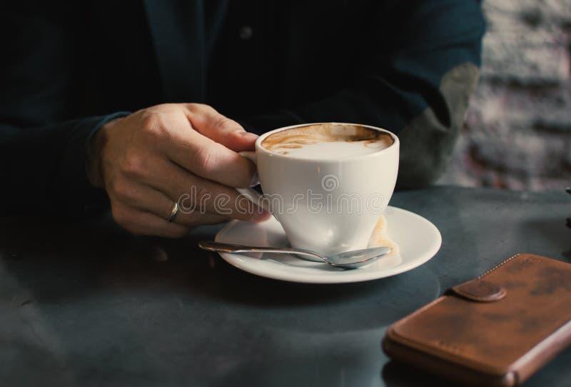 Mens die een kop van cappuccino houden royalty-vrije stock foto