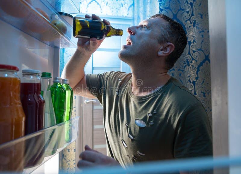 Mens die een koude fles bier van zijn koelkast drinken stock foto's