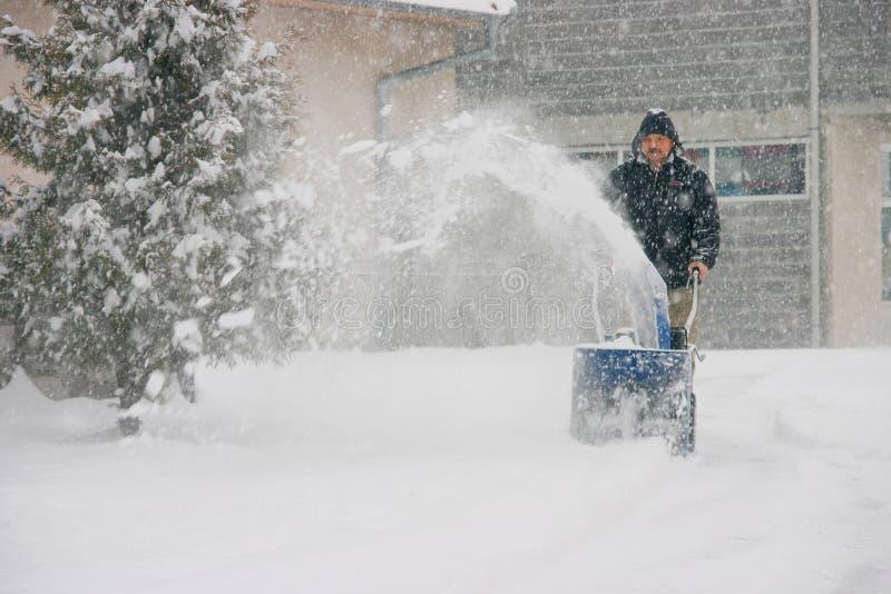 Mens die een krachtige sneeuwblazer met behulp van royalty-vrije stock afbeeldingen