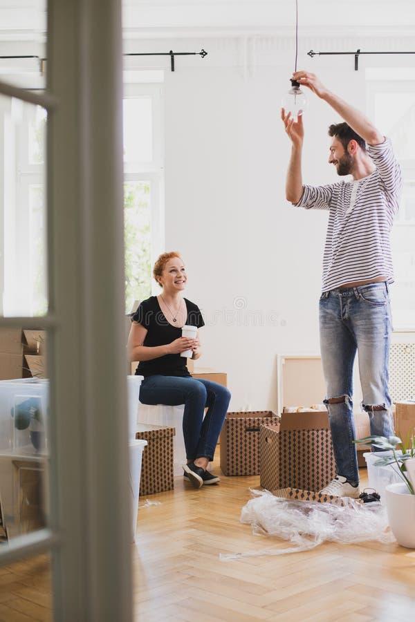 Mens die een lamp hangen terwijl het leveren van nieuw huis met zijn het glimlachen wi stock afbeeldingen