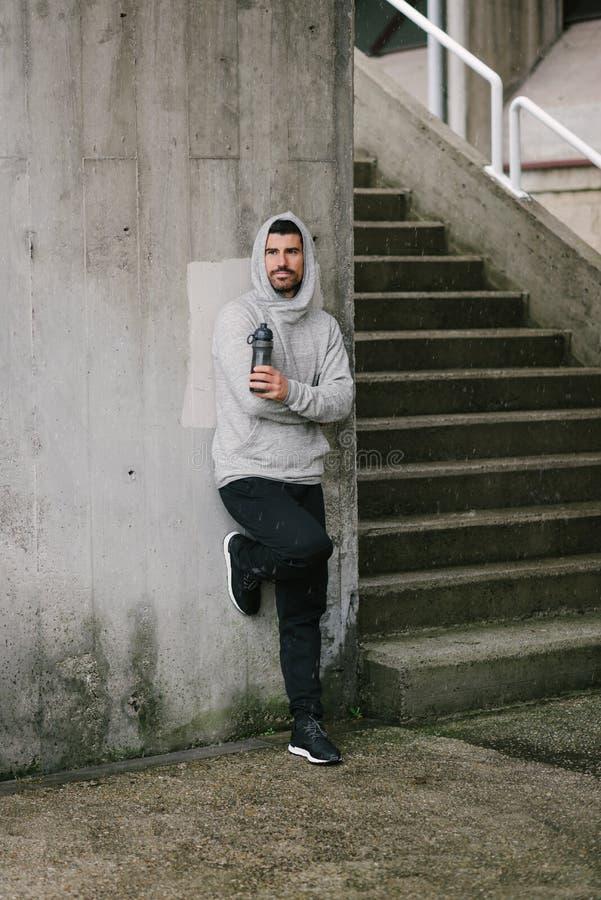 Mens die een lopende trainingonderbreking voor drinkwater nemen royalty-vrije stock fotografie