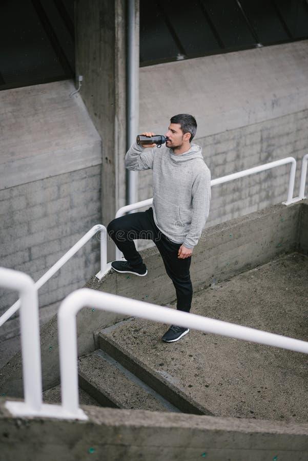 Mens die een lopende trainingonderbreking voor drinkwater nemen stock foto's