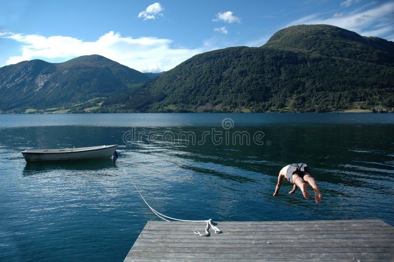 Mens die in een meer duikt stock fotografie