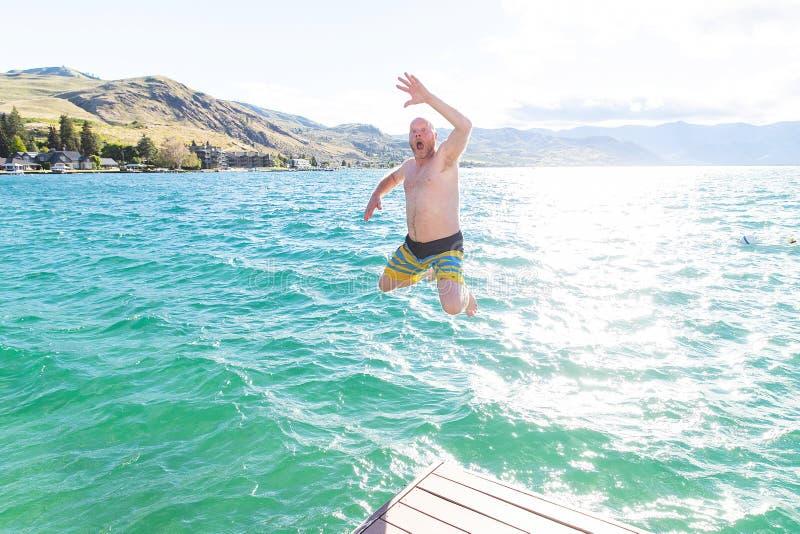 Mens die in een meer op de zomervakantie springen royalty-vrije stock foto's
