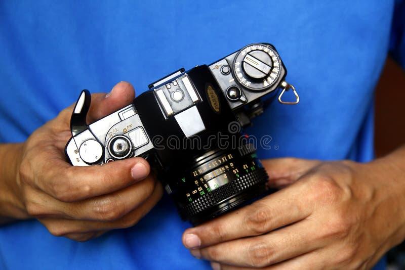 Mens die een 35mm handfilmcamera houden stock foto