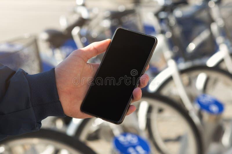 Mens die een mobiele telefoon voor fietspost met behulp van stock foto