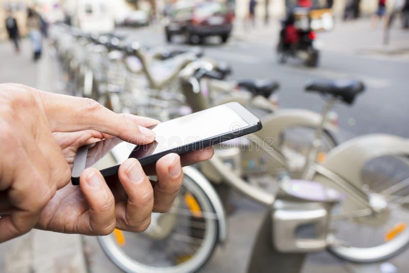 Mens die een mobiele telefoon voor Velib-Post, Parijs met behulp van stock foto
