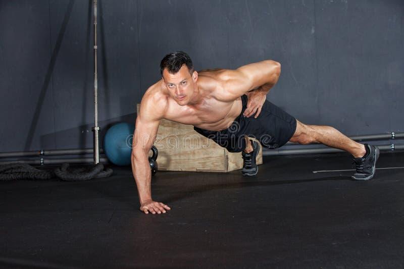 Mens die een opdrukoefening op één wapen in een gymnastiek doen royalty-vrije stock foto's