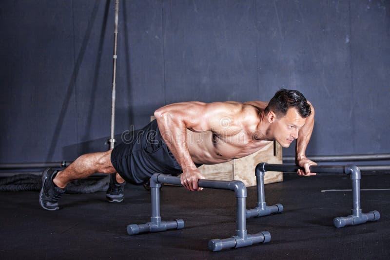 Mens die een opdrukoefening op één wapen in een gymnastiek doen stock afbeeldingen