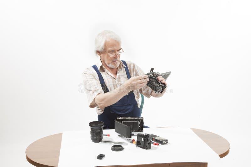 Mens die een oude camera herstellen stock foto