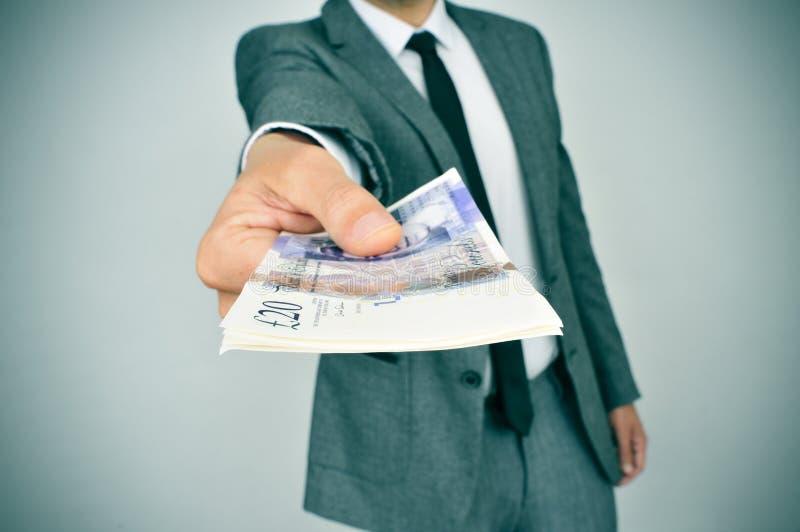Mens die een pakje van pond Sterlingrekeningen geven aan de waarnemer stock afbeelding