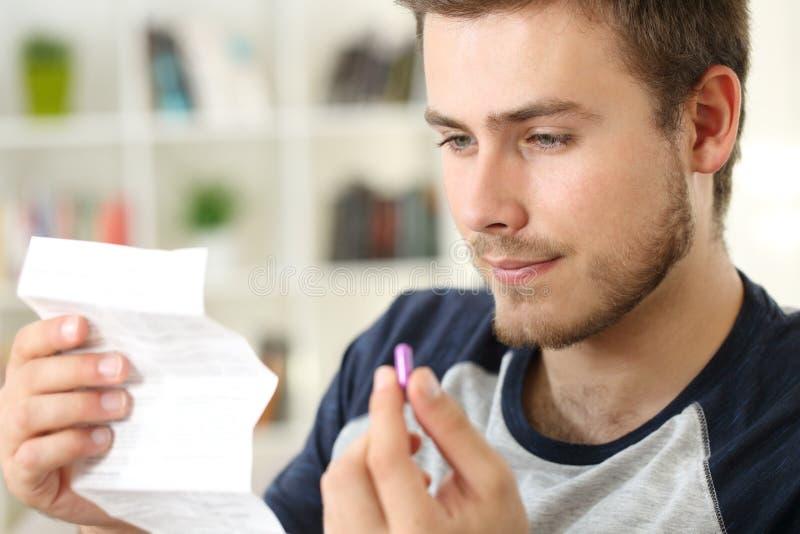 Mens die een pamflet lezen voordien om een pil te nemen stock afbeelding