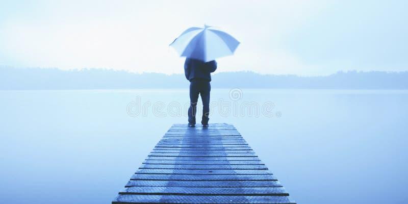 Mens die een Paraplu op een Pier houden door Rustig Meerconcept stock fotografie