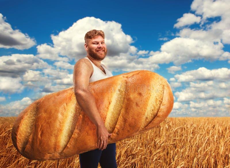 Mens die een reusachtig brood op gebied van tarwe houden stock fotografie