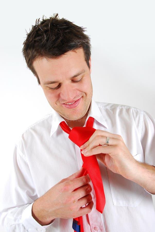 Mens die een rode stropdas bindt royalty-vrije stock foto