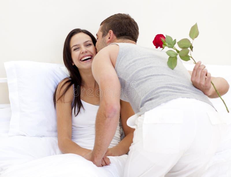 Mens die een roos en een kus geeft aan zijn mooie vrouw stock foto