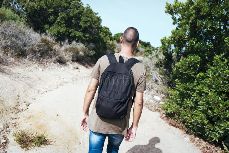 Mens die een rugzak dragen die door een landweg lopen stock afbeeldingen