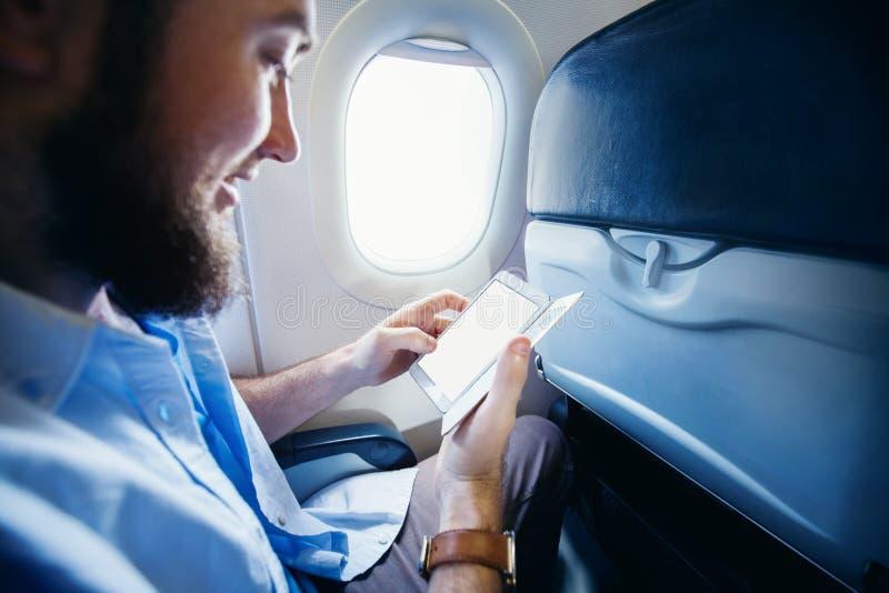 Mens die een slimme telefoon met het lege scherm in vliegtuig houden royalty-vrije stock fotografie