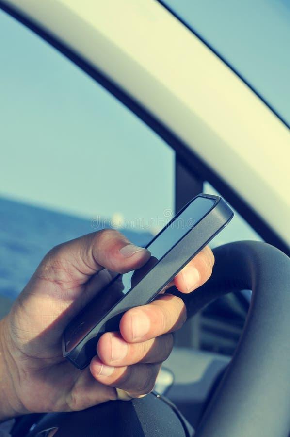 Mens die een smartphone gebruiken terwijl het drijven van een auto stock foto's