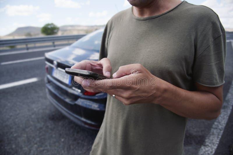 Mens die een smartphone naast een auto op de weg gebruiken stock afbeelding