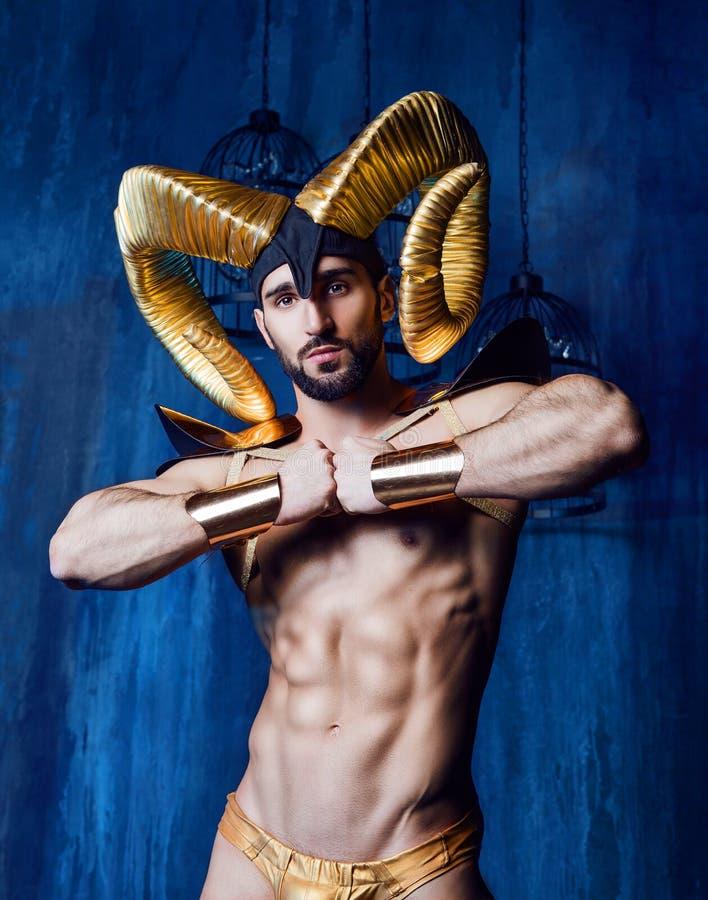 Mens die een stadiumkostuum met grote gouden hoornen dragen royalty-vrije stock afbeelding