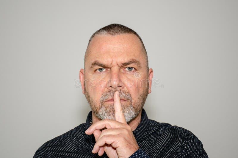 Mens die een stiltegebaar met vinger maken aan lippen stock foto's