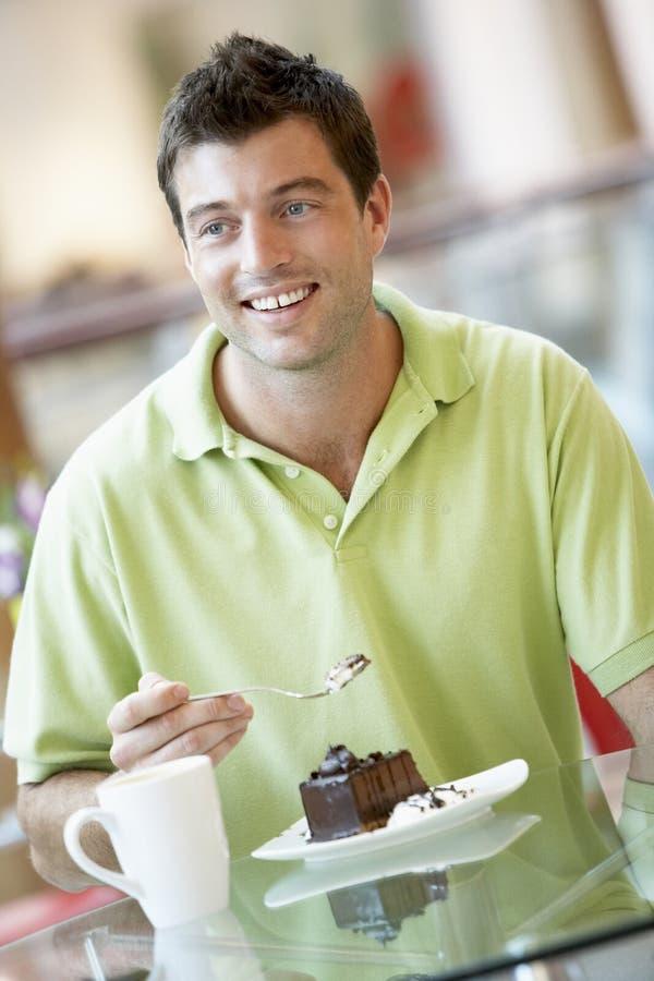 Mens die een Stuk van Cake eet bij de Wandelgalerij stock foto's
