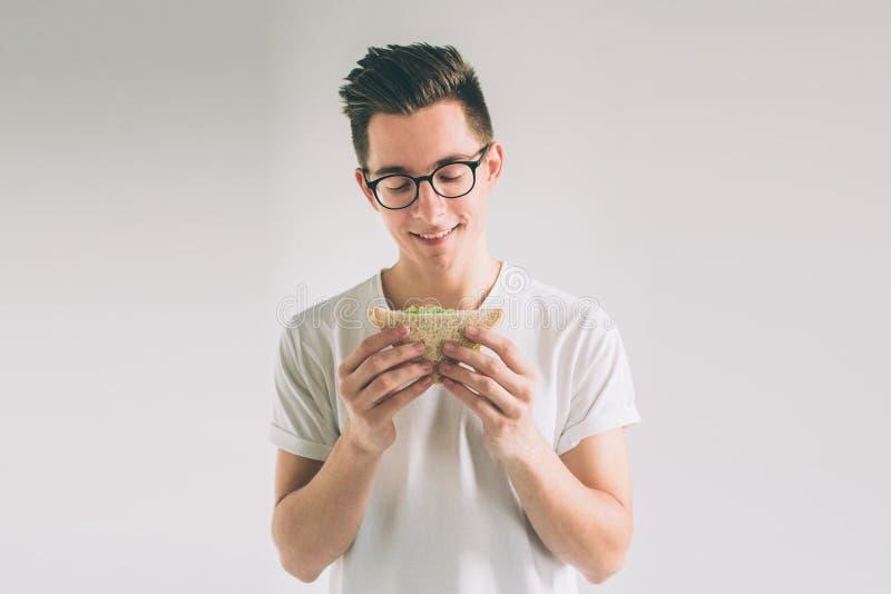 Mens die een stuk van hamburger houden de student eet snel voedsel niet nuttig voedsel Zeer hongerige mens Nerd draagt glazen stock foto