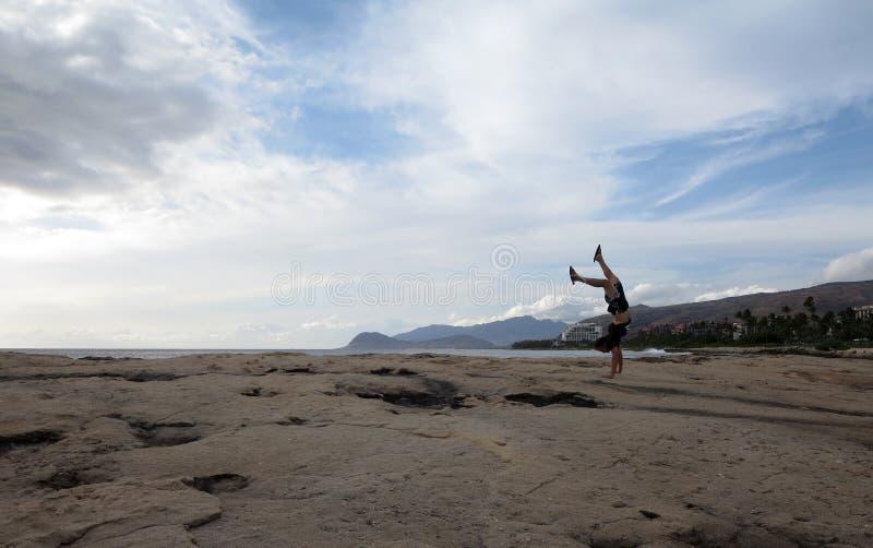 Mens die een t-shirt, borrels, en pantoffelshandstanden op kust dragen stock fotografie