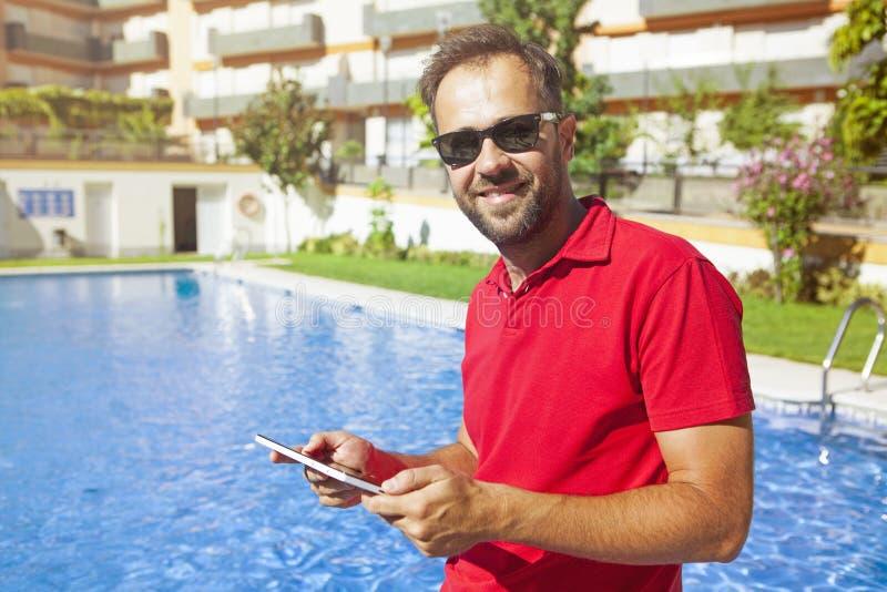Mens die een tablet gebruiken bij poolside stock foto's