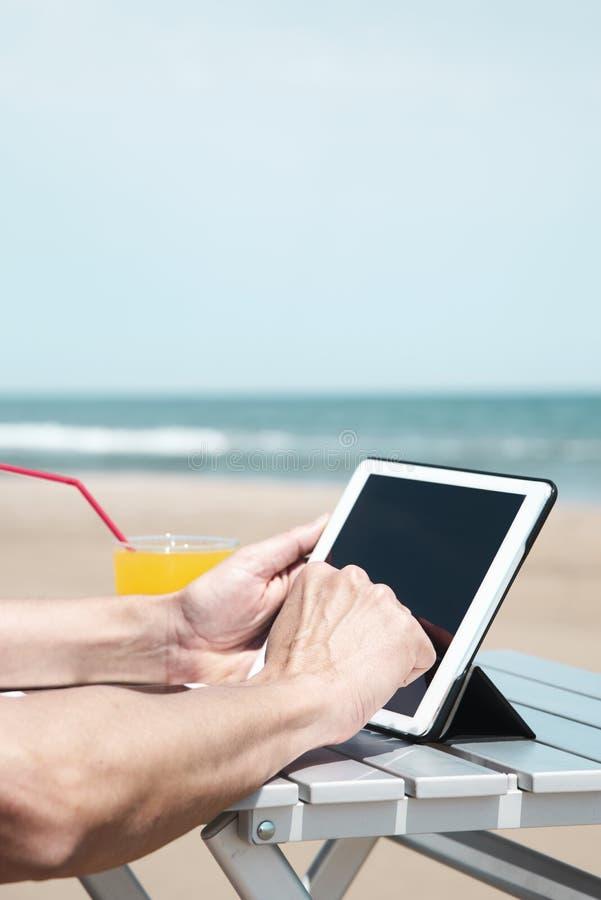 Mens die een tablet op het strand gebruiken royalty-vrije stock afbeelding