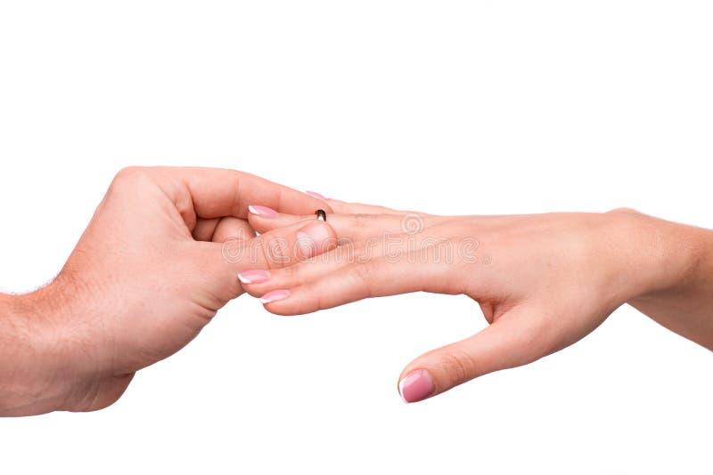 Mens die een trouwring op haar vinger zetten stock fotografie