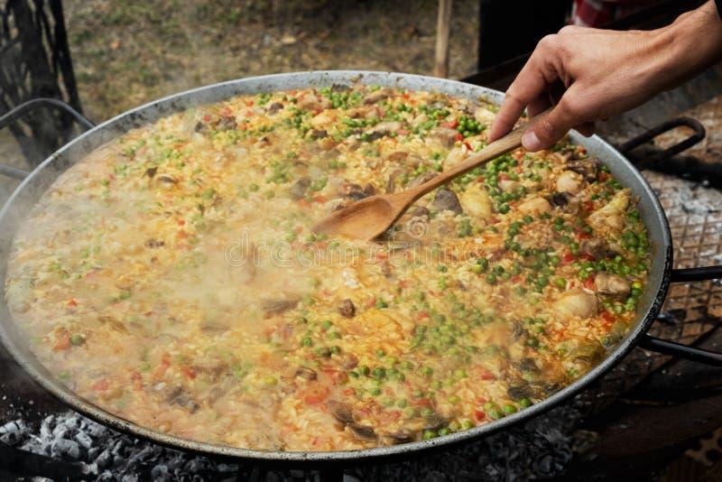 Mens die een typische Spaanse paella voorbereiden stock fotografie