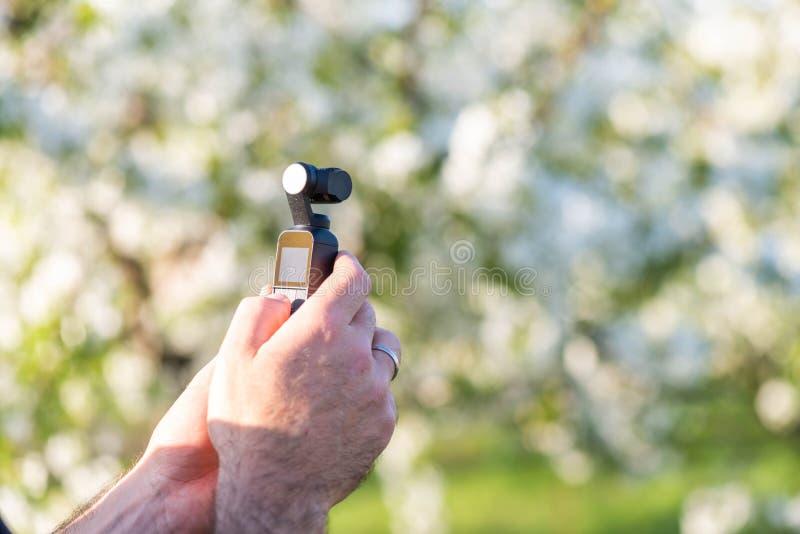Mens die een uiterst kleine moderne videocamera in een park houden De filmideeën van de de lentetijd royalty-vrije stock foto's