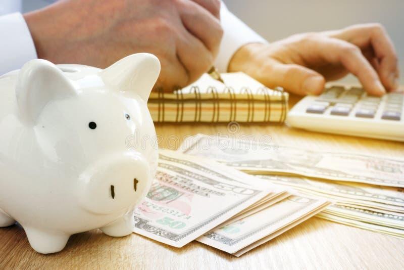 Mens die in een van de van het boekhoudingsboek, spaarvarken en dollar rekeningen schrijven 3d illustratie op witte achtergrond royalty-vrije stock foto